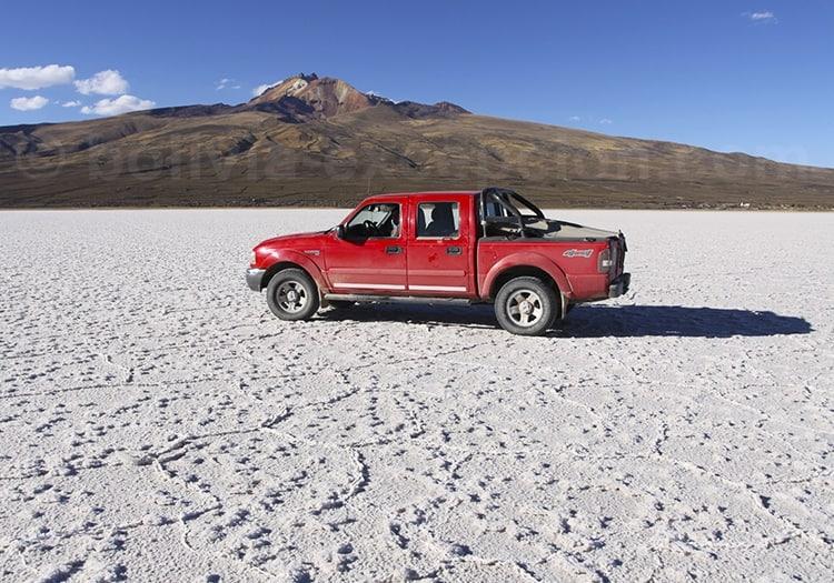 Voiture rouge sur désert de sel montagnes
