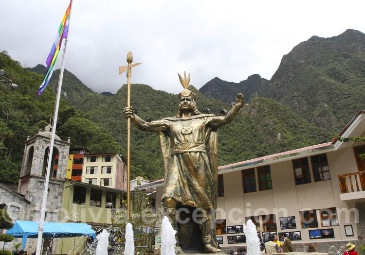 Statue en bronze sur fond de ville et montagnes